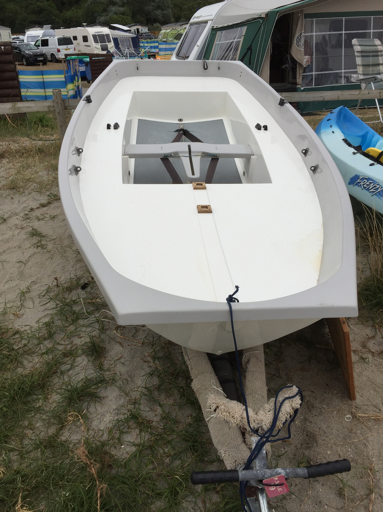 A GRP Mirror dinghy hull, with no rig, sails or foils, on a beach