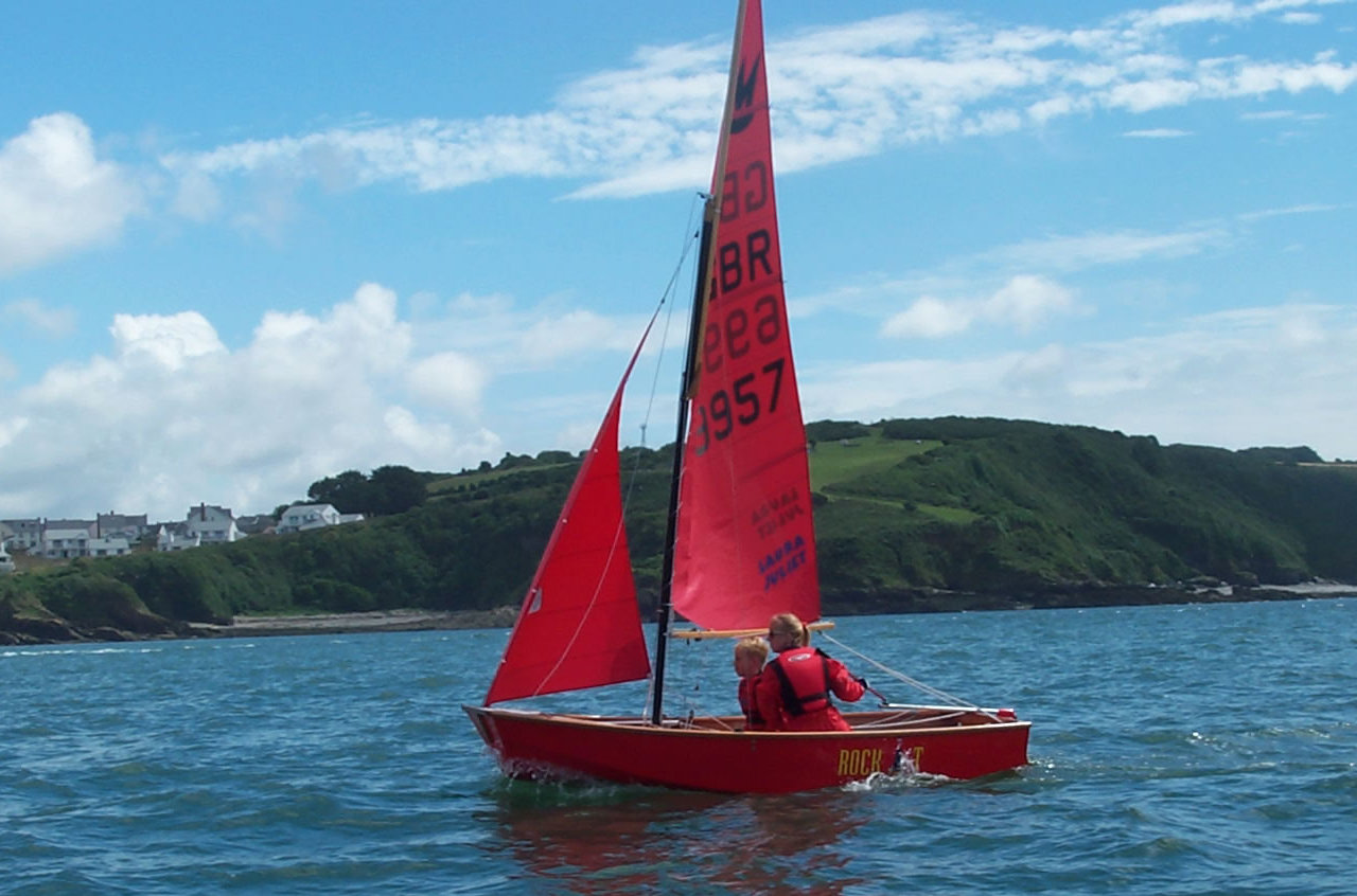Red Mirror dinghy being helmed by a mum with her young son crewing