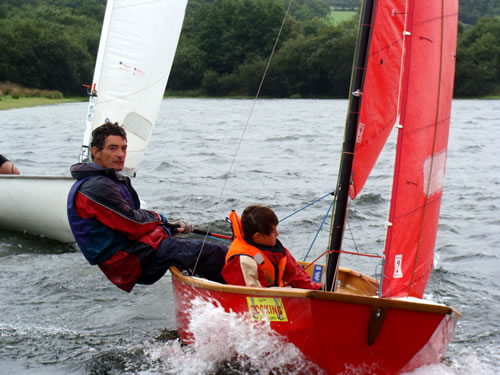 Red Mirror dinghy being sailed by father & son