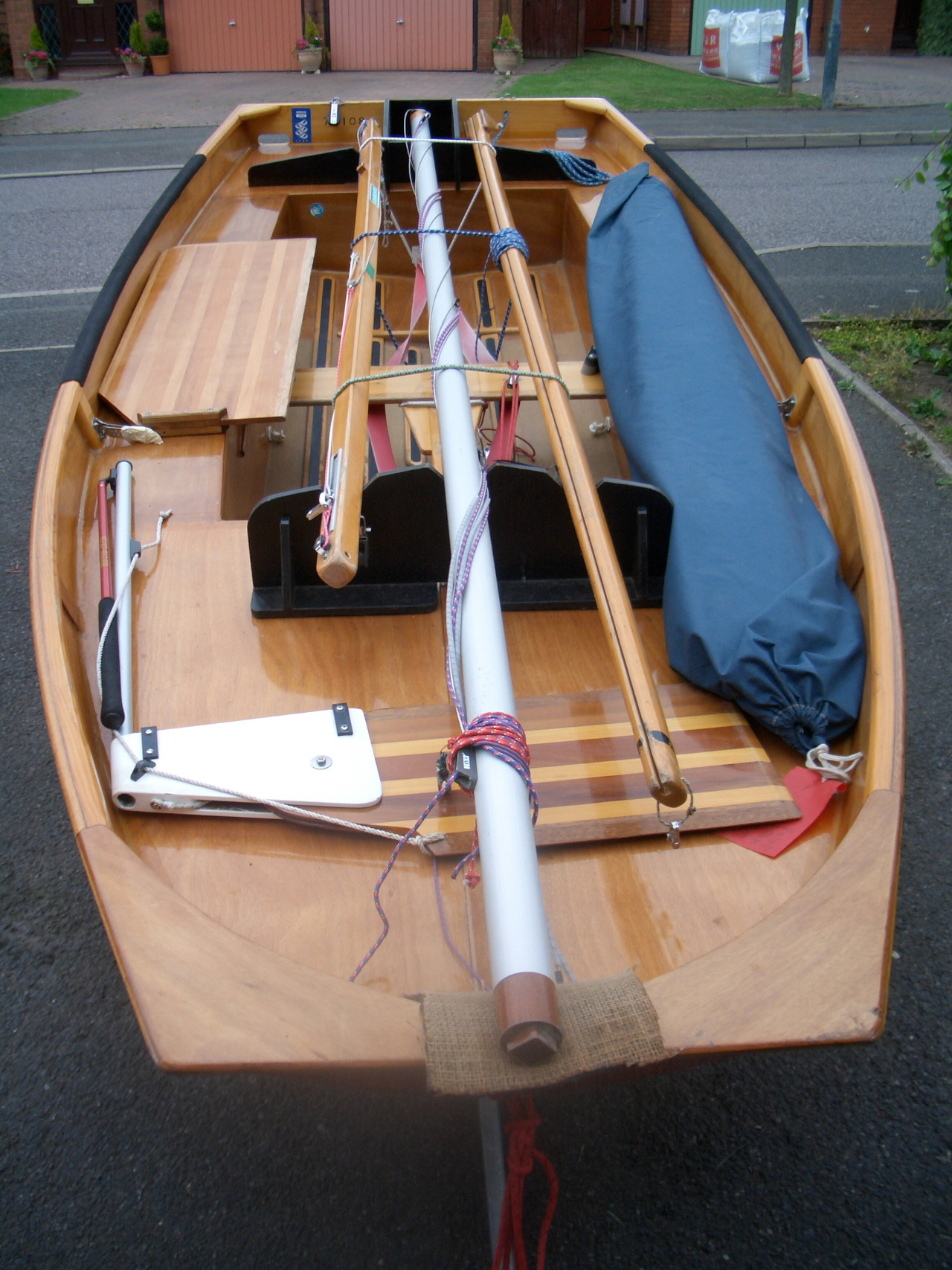 A red wooden Mirror dinghy with mast down on a driveway, bow towards the camera