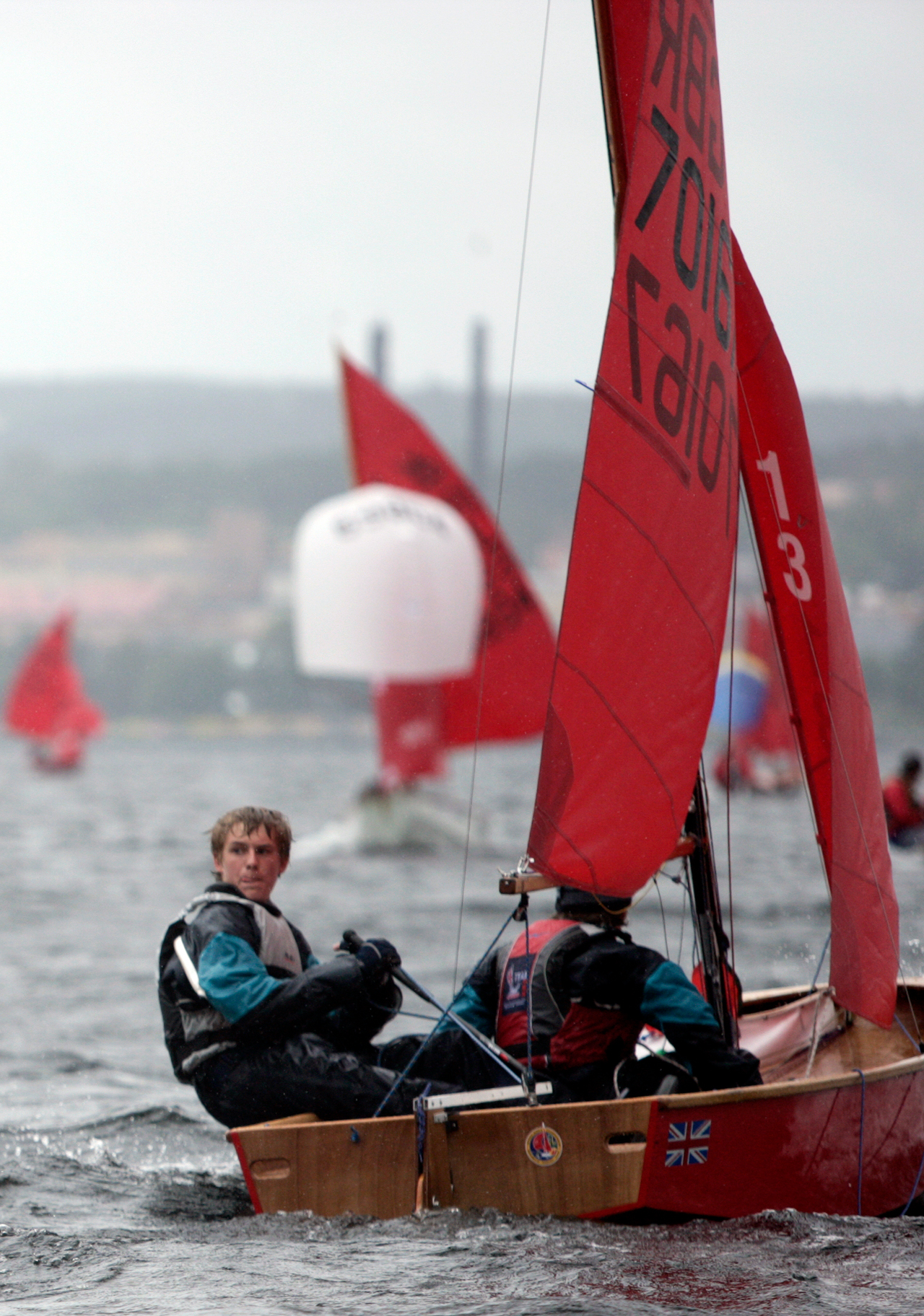 A red Mirror dinghy racing with helm looking to see if he can tack