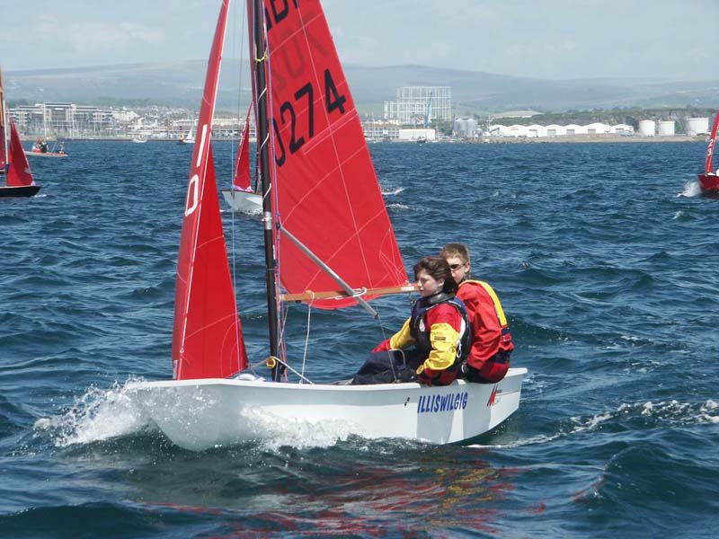 A white GRP Mirror dinghy racing to windward crewed by brother and sister sailing towards the camera
