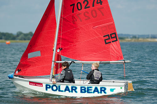A white GRP Mirror dinghy being sailed by two small boys