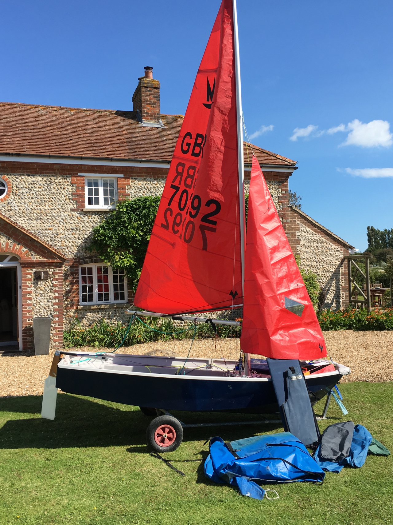 A Mirror dinghy rigged  up outside a house