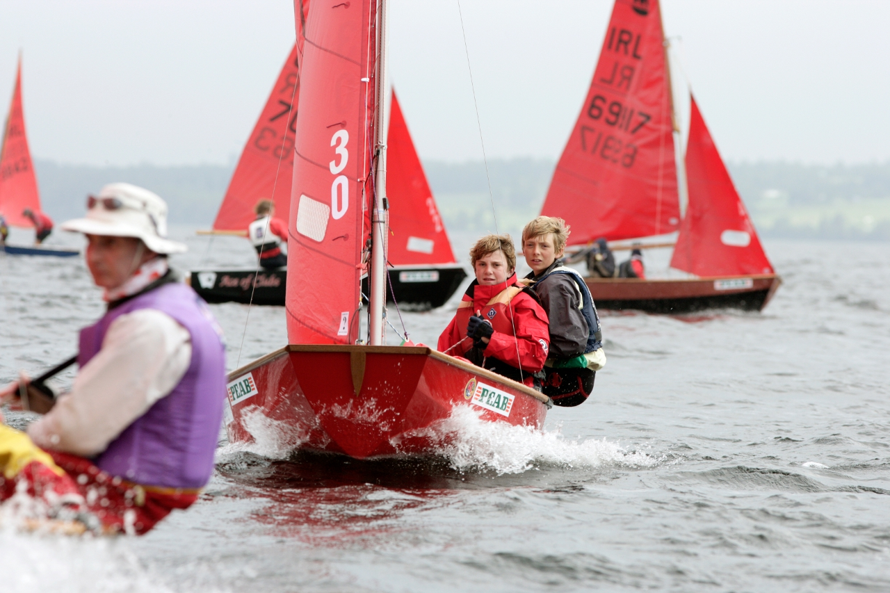 A red Mirror dinghy sailing on a lake
