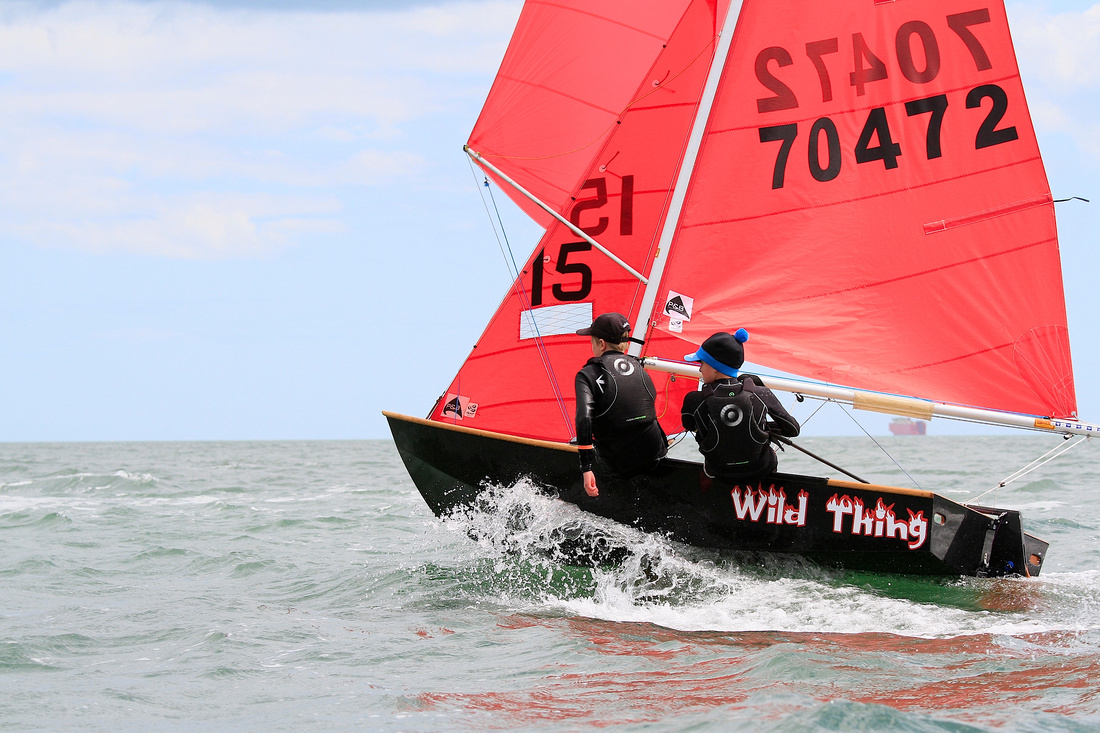 A black wooden Mirror dinghy reaching at speed with spinnaker up