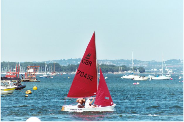 A white Mirror dinghy sailing on a sunny day