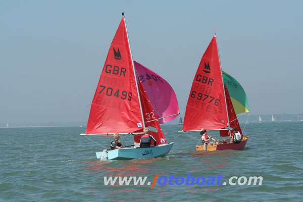 Light blue GRP Mirror dinghy with spinnaker hoisted