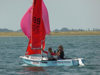 A blue grp Mirror dinghy being sailed downwind, with spinnaker, by two girls