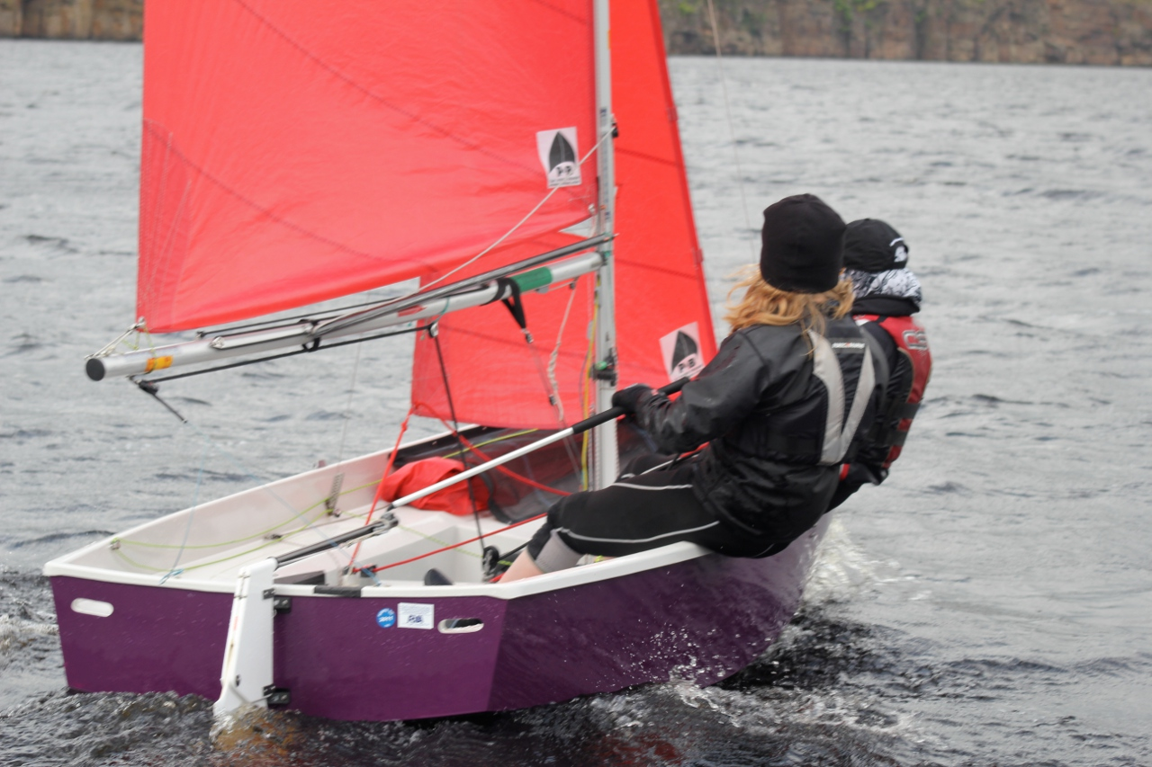 A purple GRP Mirror dinghy sailing upwind with crew on the gunwale
