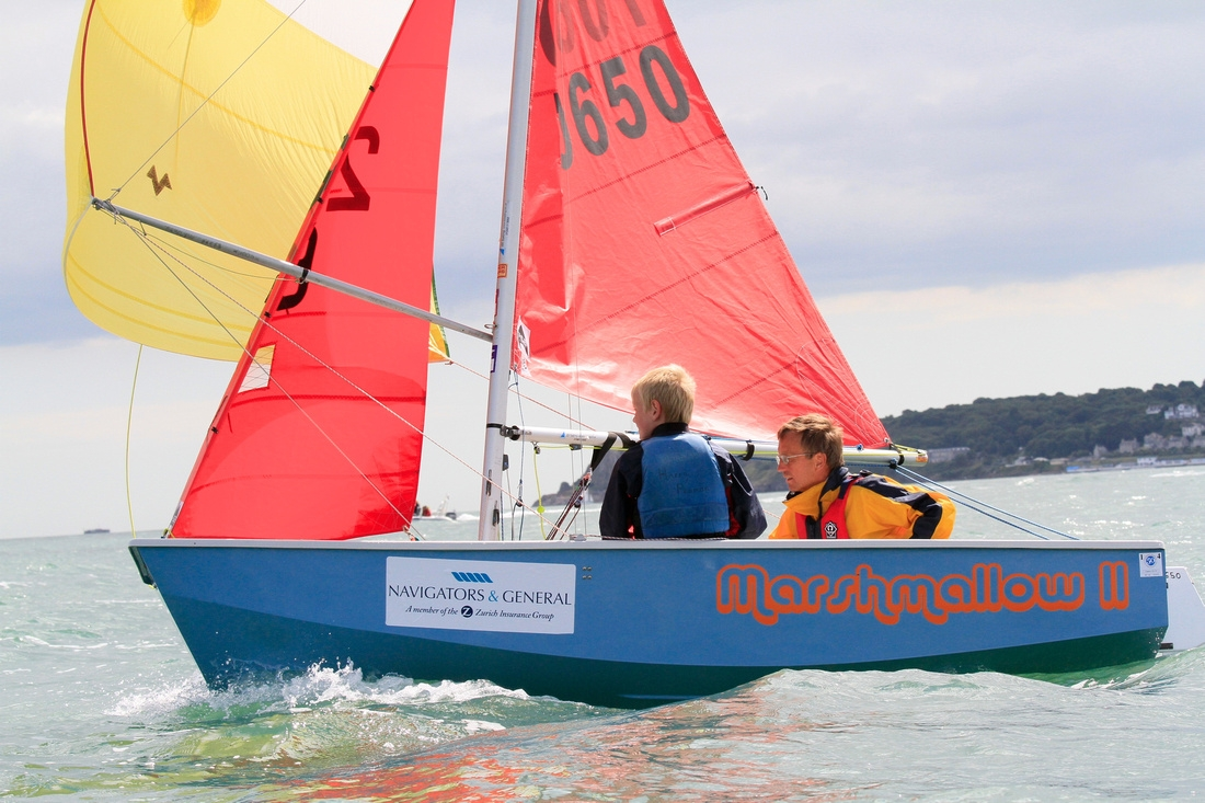 A light blue GRP Mirror dinghy racing on a reach with spinnaker flying