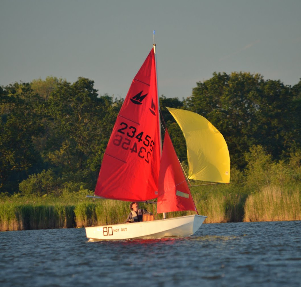 A white GRP Mirror dinghy sailing single handed on a Norfolk Broad with yellow spinnaker set and a reed bank in the background
