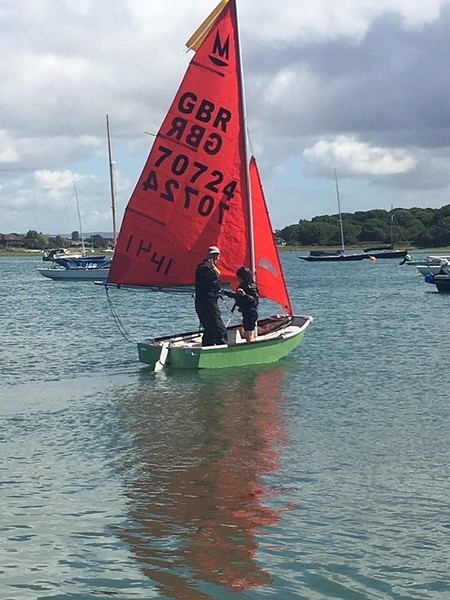 A green GRP Mirror dinghy being sailed
