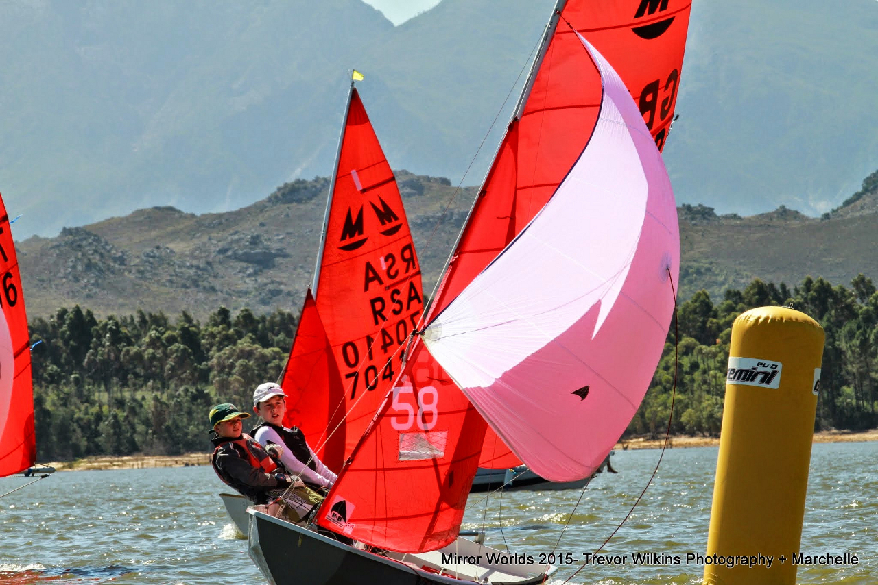 A grey Mirror Dinghy on a  spinnaker reach sailed by two boys