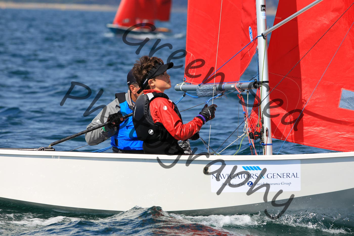 A close up of the helm and crew of a white Mirror dinghy racing under spinnaker