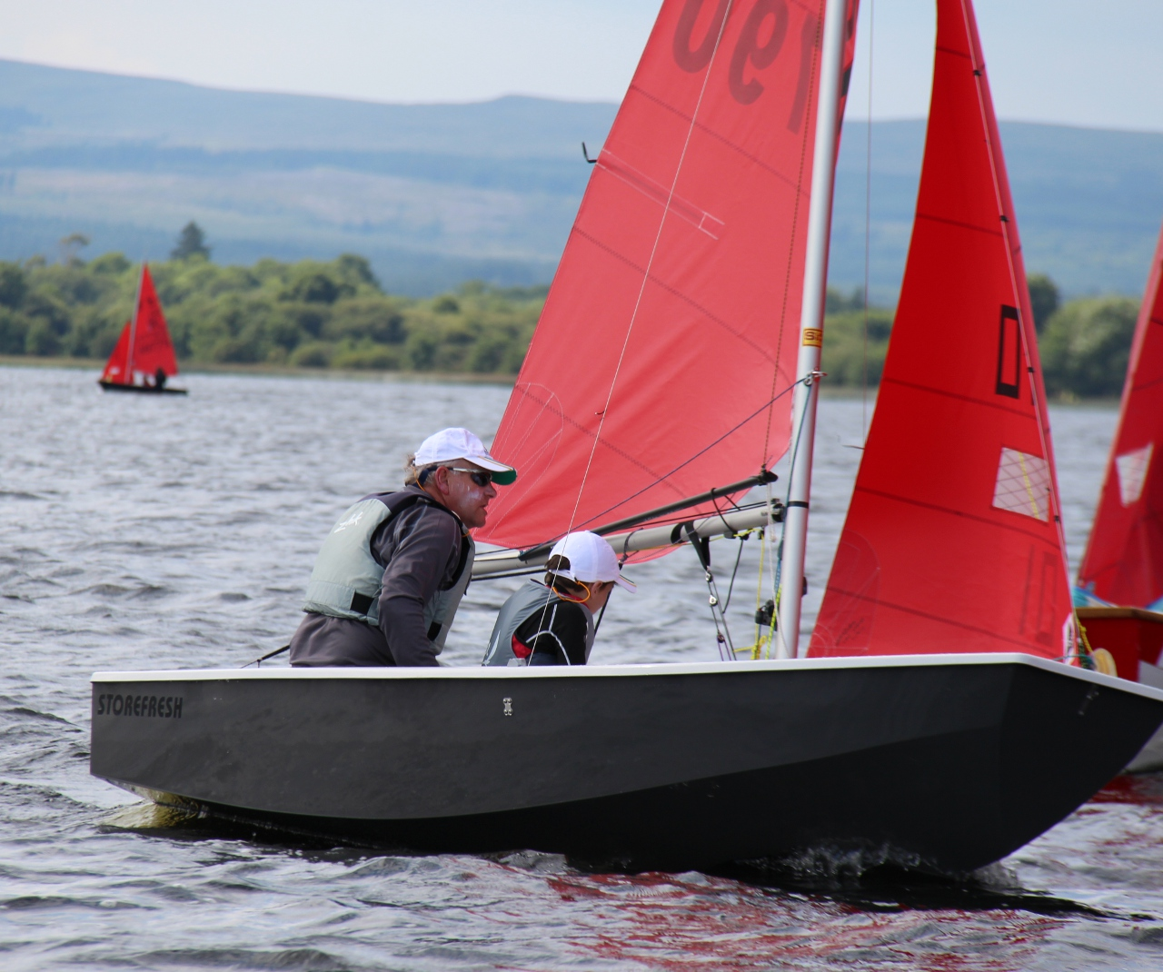 Grey GRP Mirror dinghy sailing on Lough Derg in southern Ireland