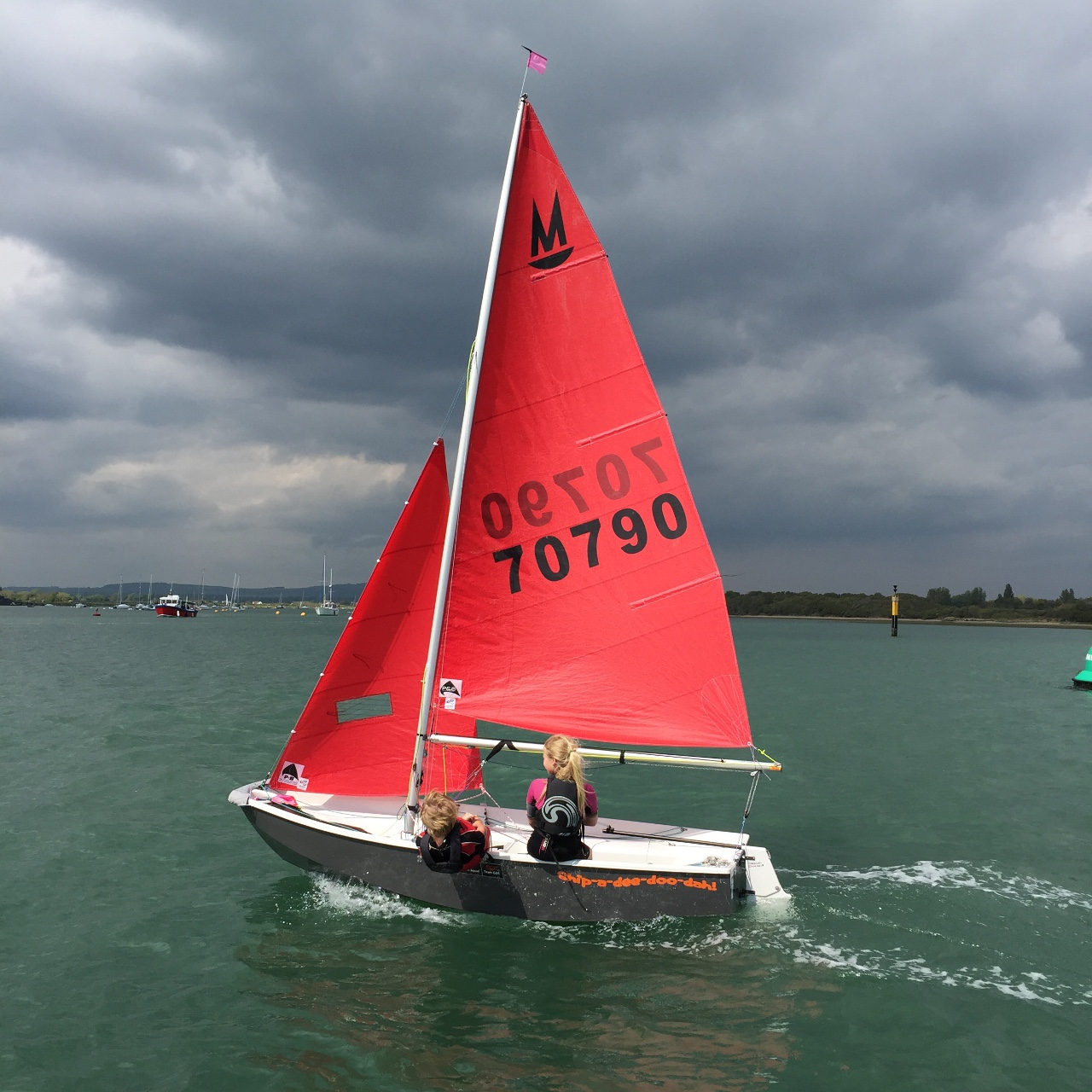 A grey GRP Mirror dinghy being sailed by two children