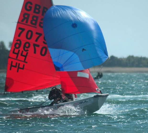 A white GRP Mirror dinghy with blue spinnaker planing fast