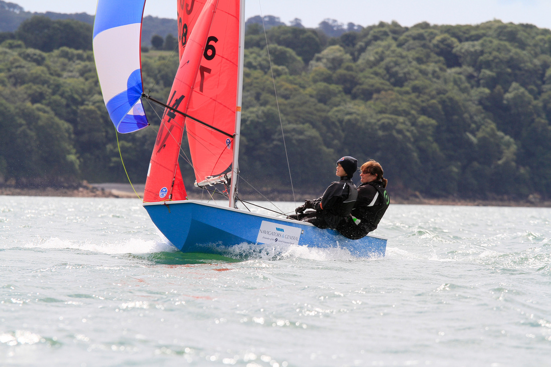 A blue GRP Mirror dinghy racing on a reach with spinnaker set