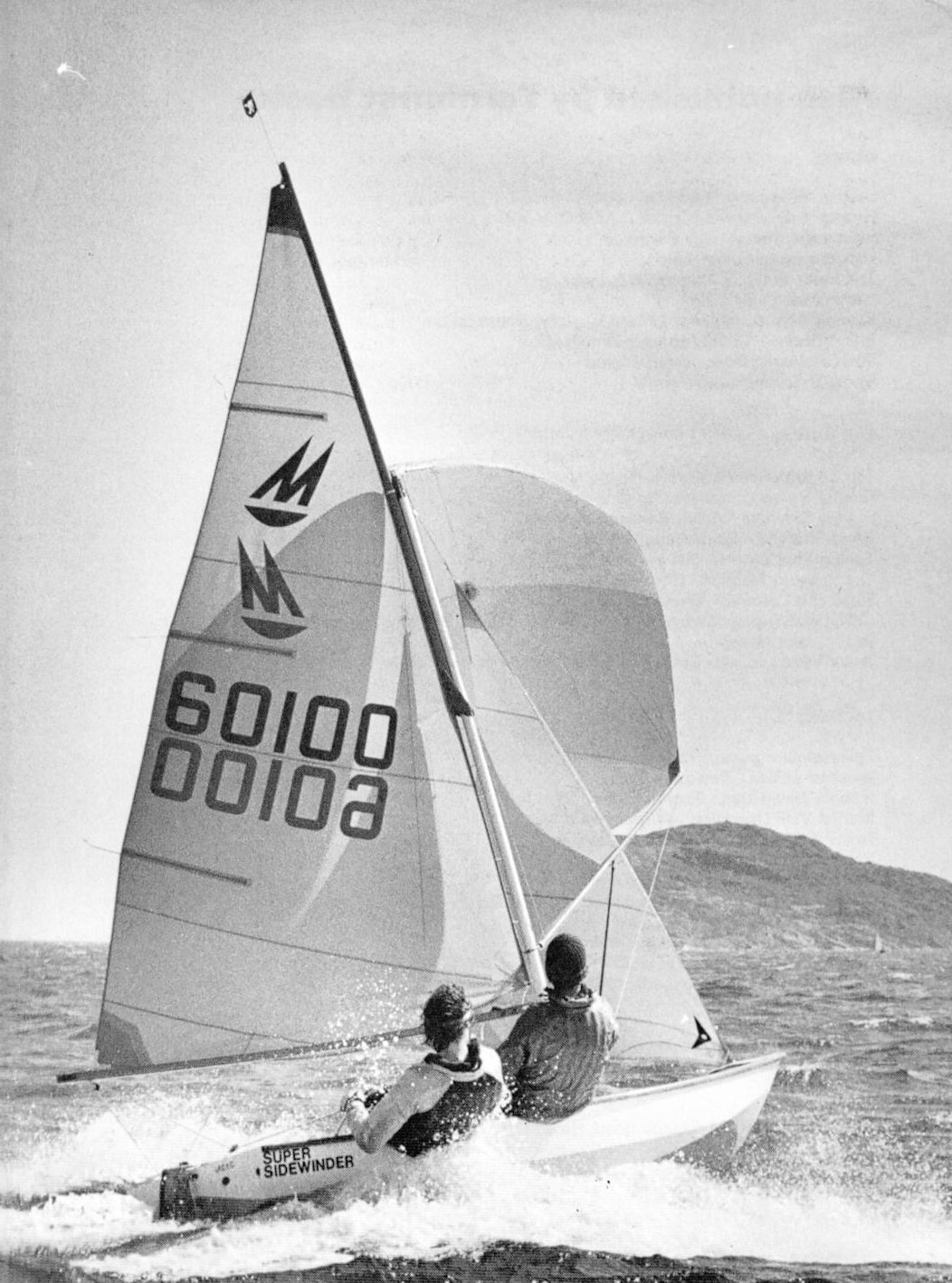 A Mirror dinghy racing on a reach with spinnaker set on a windy day, helm and crew both sitting out and the gaff pulled right up with no gap between the mast and the gaff
