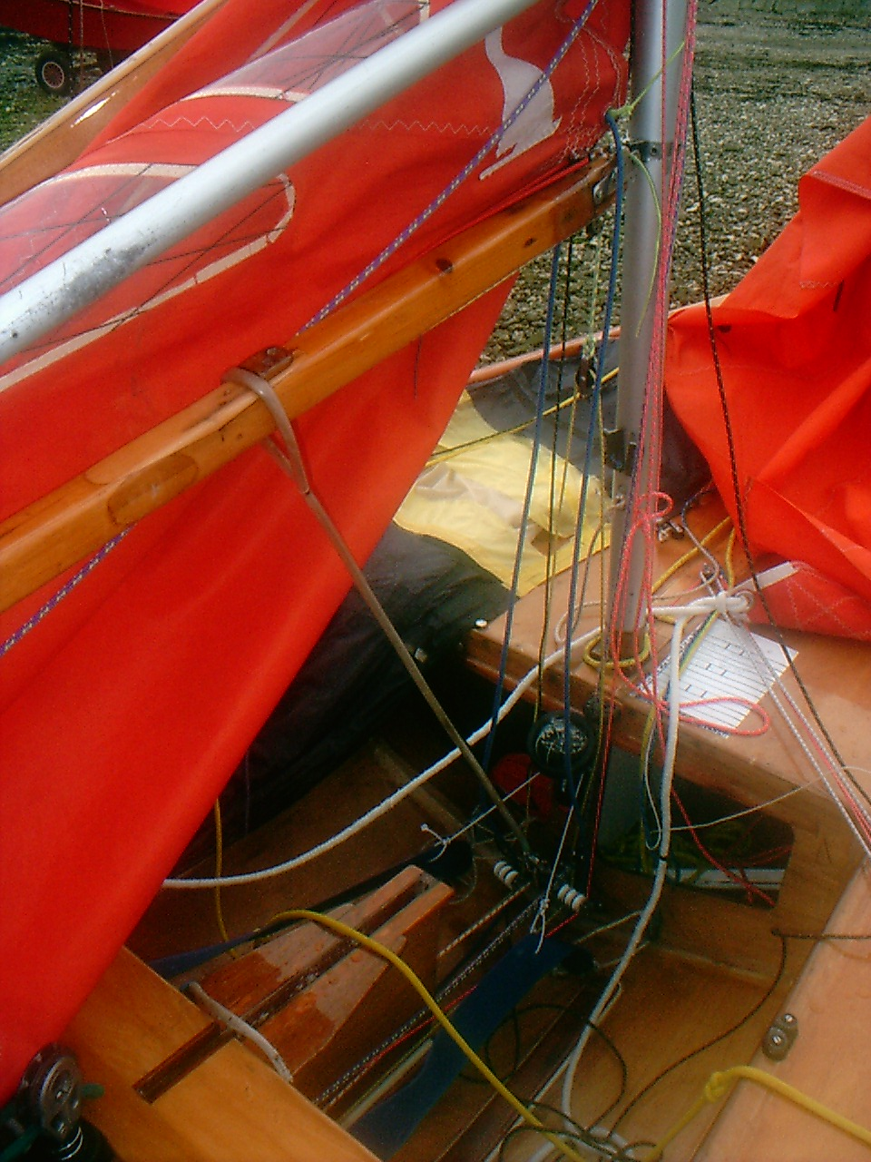 A wooden boat with sails lowered and the camera pointing towards the bottom of the stowage bulkhead