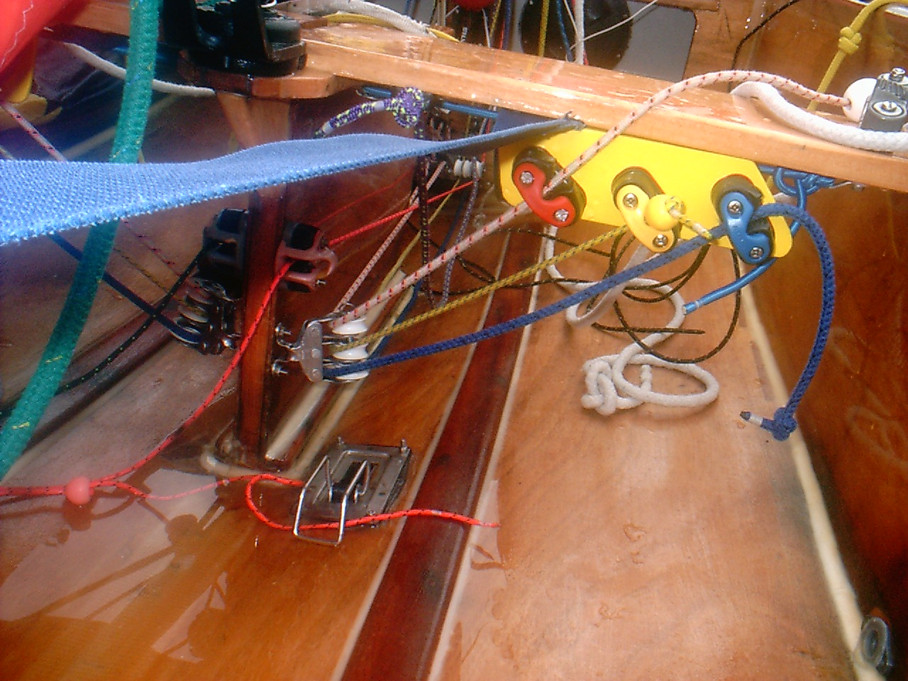 Three mailsail control lines running through triple blocks and up to cleats on the back edge of the thwart on a Mirror dinghy