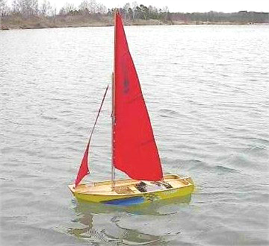 A one sixth scale model of a Mirror dinghy sailing on a lake